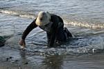 Pflege des Fischernetzes am Strand.